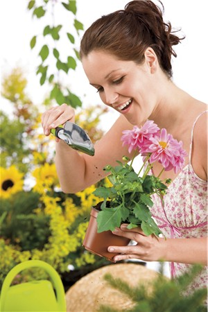 Gardening - woman holding flower pot and shovel